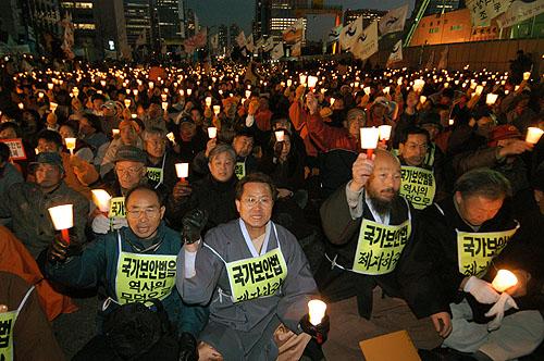 '그해 겨울은 몹시 추웠다.' 2004년 12월 1만여명이 참석한 가운데 국회 앞에서 열린 국가보안법 폐지를 요구하는 촛불집회에서 권오헌 명예회장이 농성에 들어갔다. 이후 농성자들은 국가보안법 폐지를 요구하는 집단 삭발과 함께 1천명 단식농성에 돌입했다. [통일뉴스 자료사진]