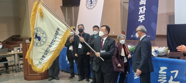 이규재 명예의장이 이태형 의장에게 범민련 남측본부 깃발을 전달했다. [사진 - 범민련 남측본부]