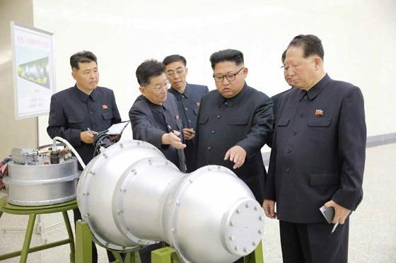 ▲ 2017.9.3. 북은 대륙간탄도미사일(ICBM)에 장착하는 초강력 폭발력을 가진 열핵무기라 일컫는 수소탄 시험에 성공했다고 발표했다. 사진은 김정은 국무위원장이 핵무기연구소를 찾아 핵무기병기화사업을 현지지도하며, 새로 제작한 대륙간탄도미사일(ICBM) 장착용 수소탄을 살펴보는 모습. 뒤에 세워둔 안내판에 '화성-14형'의 '핵탄두(수소탄)'라고 적혀있다. [자료사진-통일뉴스]